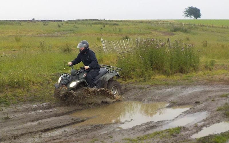 Quad bike racing through a muddy track, covered in puddles.