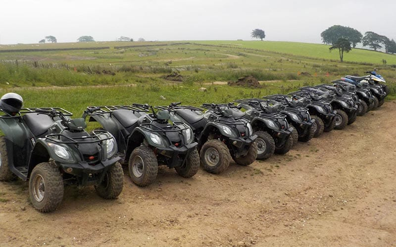 Row of quad bikes lined up on the edge of a mud path with the fields in the background.