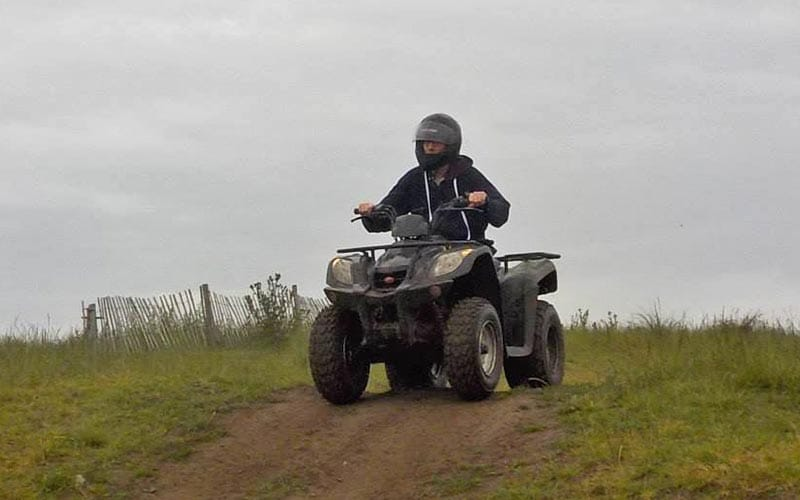 Person riding a quad bike over the top of a mound with a grey cloudy sky in the background.