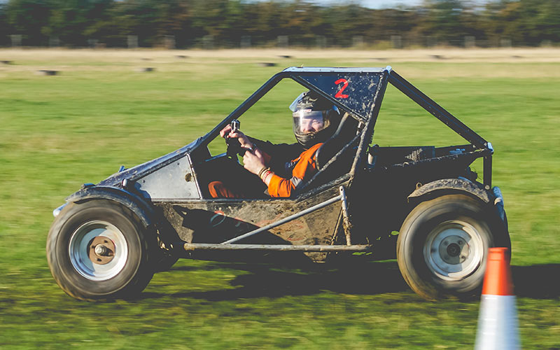 A man wearing orange overalls, driving a rage buggy through a field