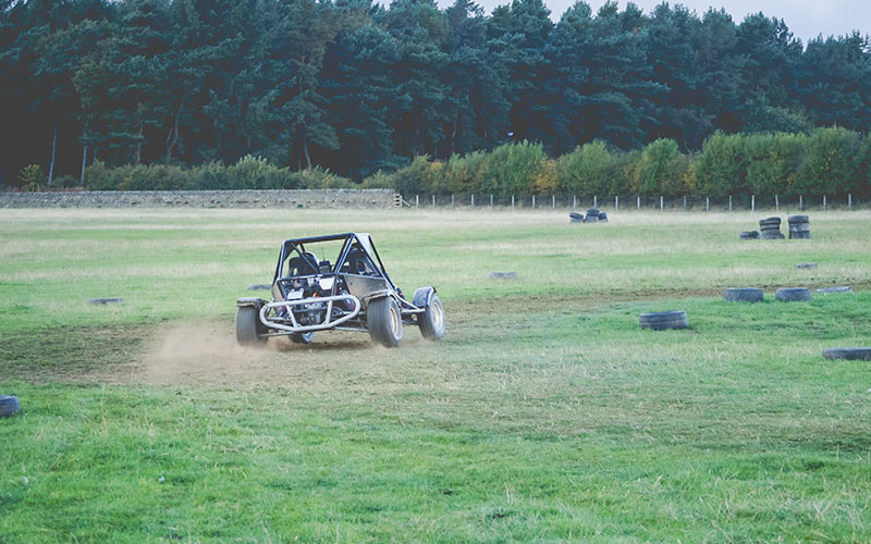 Two people in a rage buggy skidding around a corner