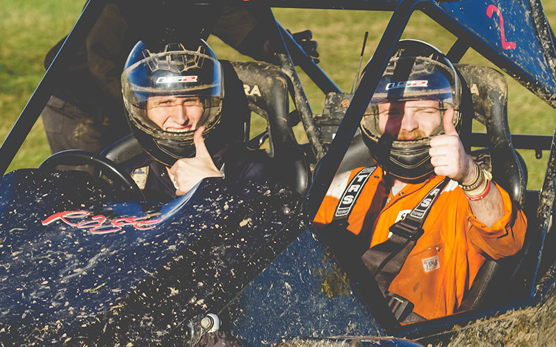 Two men with their thumbs up, sitting in a rage buggy