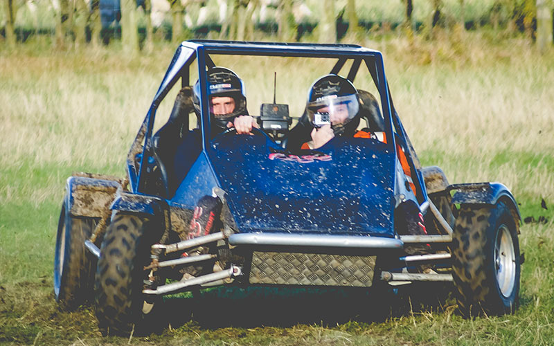 Two men driving a rage buggy in a field