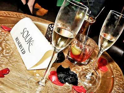 Two empty champagne flutes on a table, next to an SO.UK reserved sign