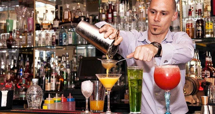 Image of a bar tender making cocktails in different shaped glasses pouring a cocktail through a sieve
