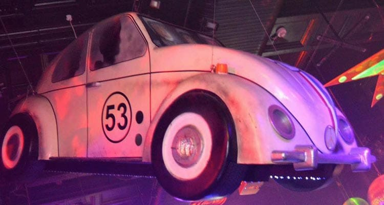 Image of a white beatle car hanging from the ceiling in a bar