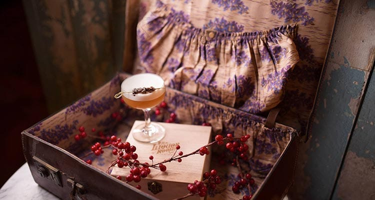Image of a suitcase with lavender fabric stitched inside full case with a small wooden box with red berrys around and a cocktail on top