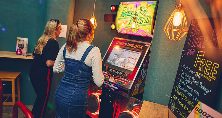 Two girls playing arcade games at Yard & Coop Liverpool