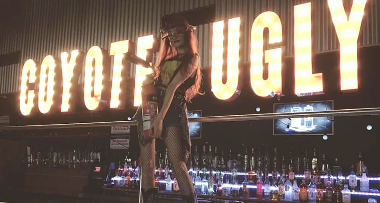 A girl dancing on a bar with a lit 'Coyote Ugly' sign in the background