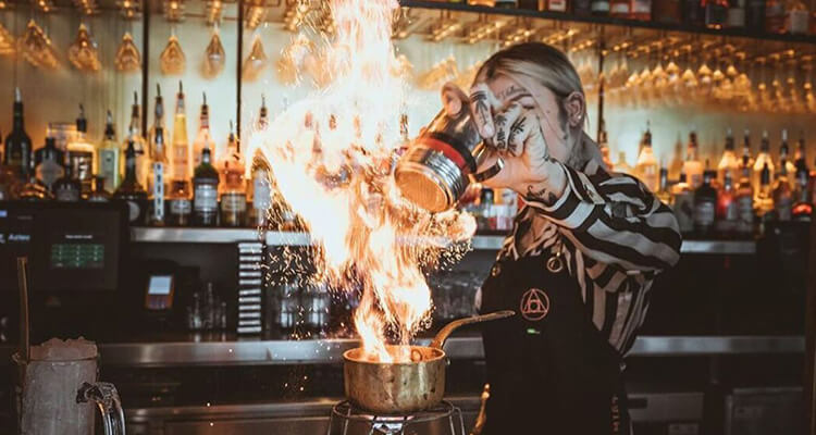 A bartender creating a drink behind the bar, with flames coming out