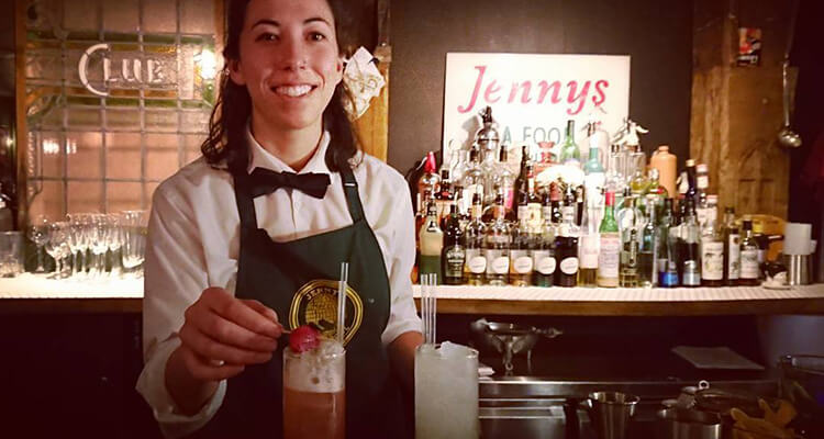A bartender serving a drink behind the bar at Jennys