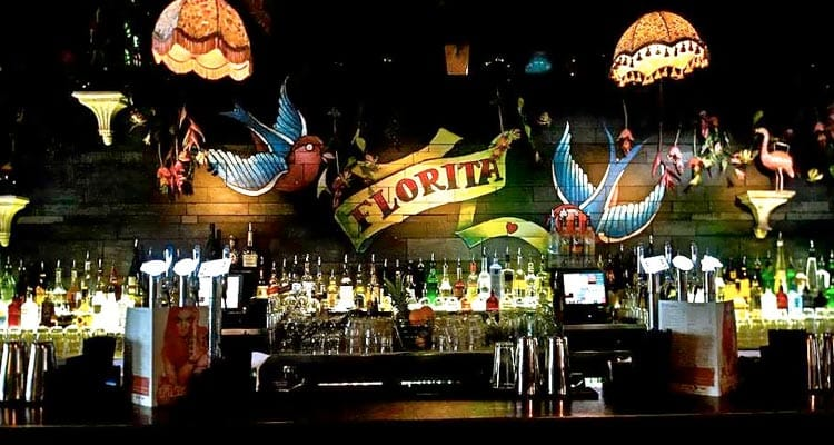 Image of the bar with spritis and glasses on the back of bar with the floritas logo on the wall with two blue doves and two lamp shades