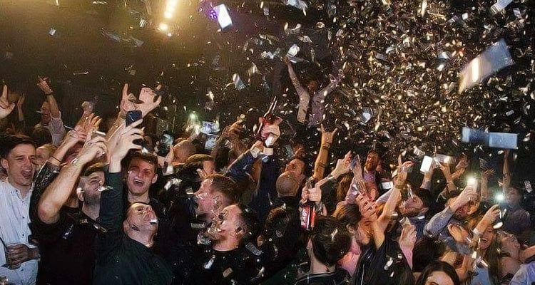 Image of people jumping and cheering inside tiger tiger with confetti coming down onto them