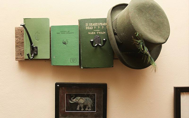 A hat hung on a coat hanger made from classic books