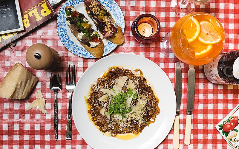 Two dishes of food on a red and white checked table cloth, next to a glass of orange
