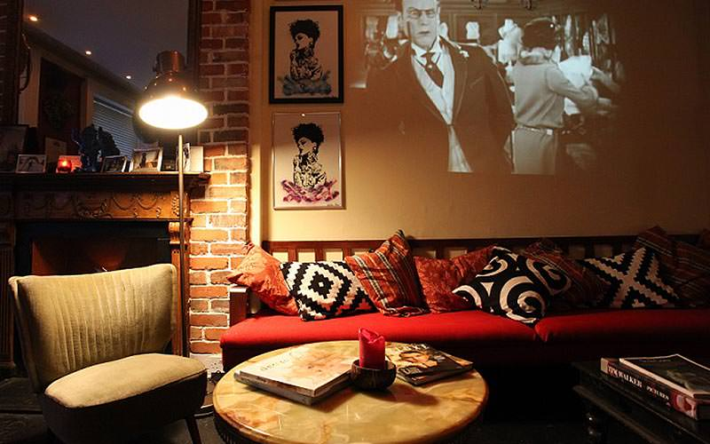 A black and white film on a screen above a sofa with patchwork cushions
