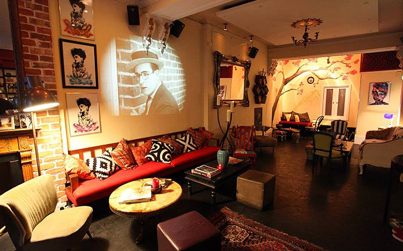 A black and white film scene projected onto a wall above various seats and tables in The Little Yellow Door, London