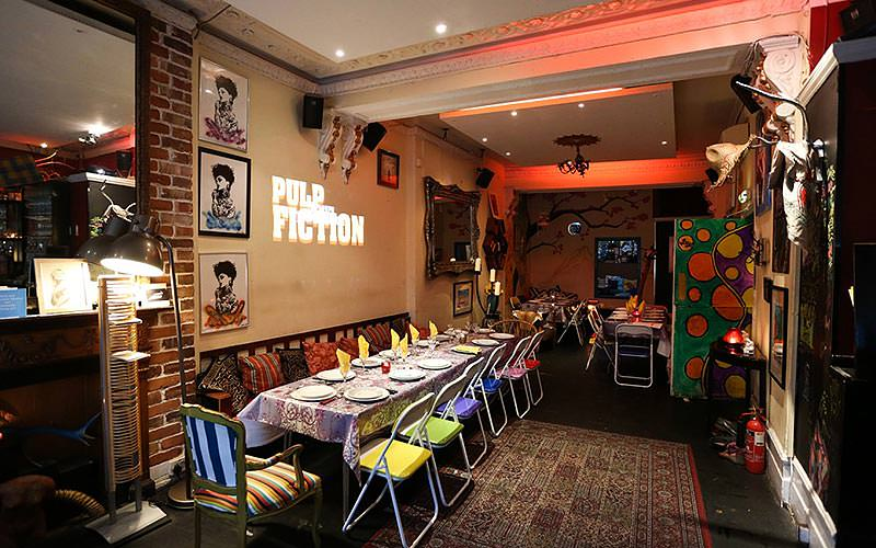 A long table set for dinner in Little Yellow Door, with the logo of the film Pulp Fiction projected on the walls