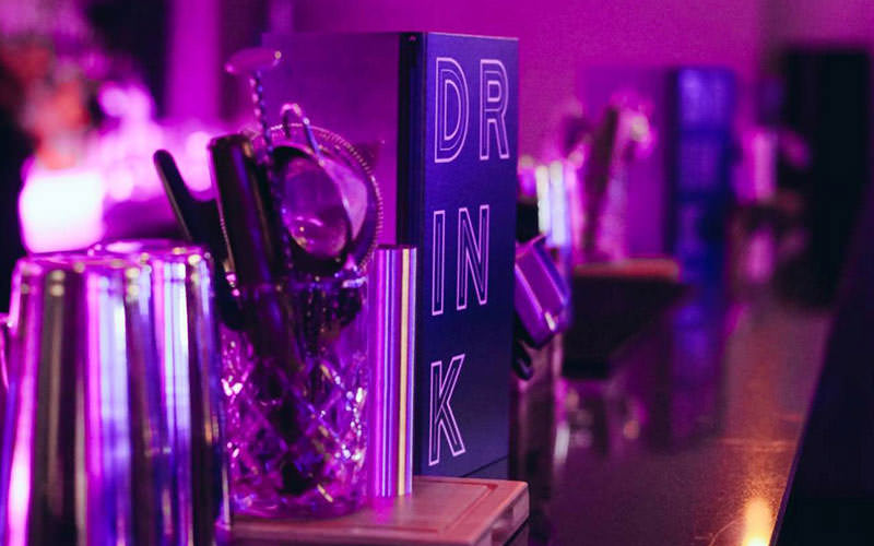 Drinks menu and cocktail stirrers on a bar