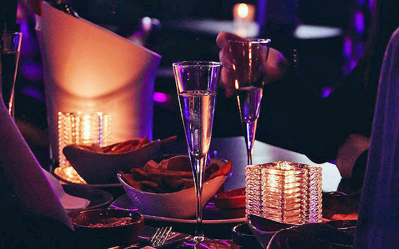 elegant champagne flutes on a table with snacks and nibbles in a nightclub