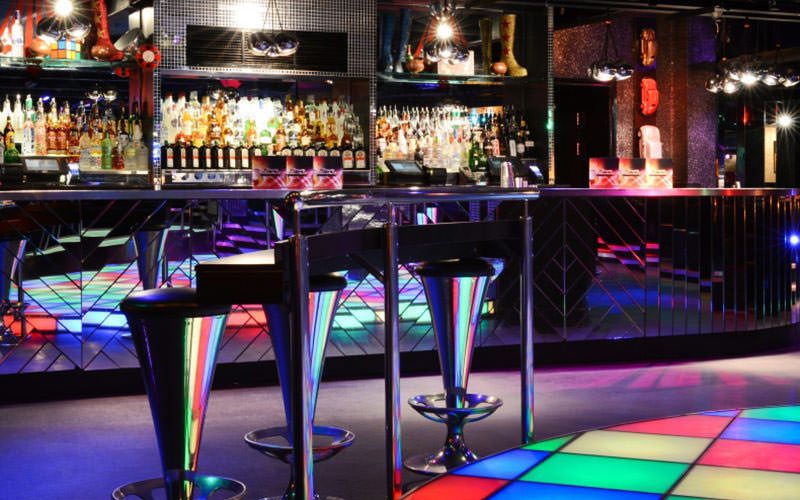 Mirrored bar with multicoloured dancefloor and some metal seats in the foreground