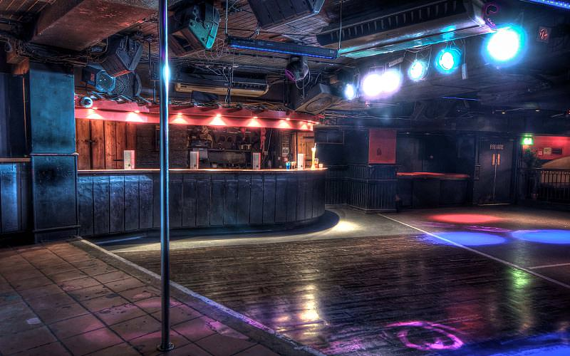 A large dance floor, with a pole in the foreground, and a bar in the back