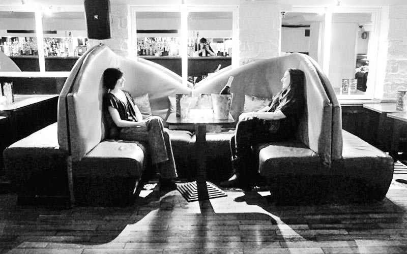 Black and white image of two women sat in a booth