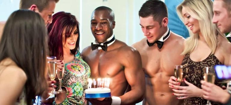 A woman receiving a cake from two butlers