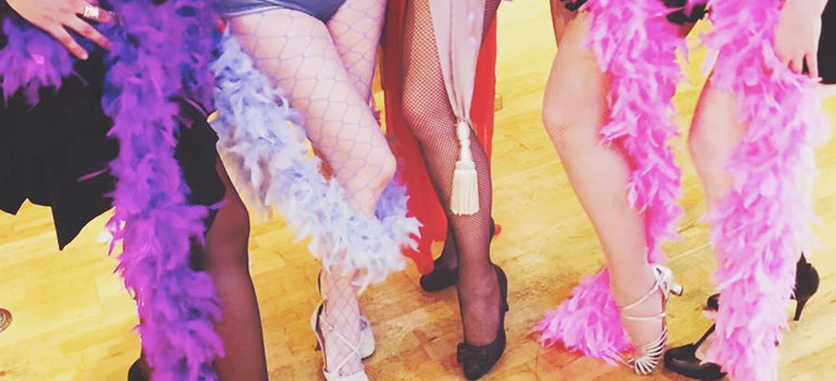 A close up of women's legs with feather boas