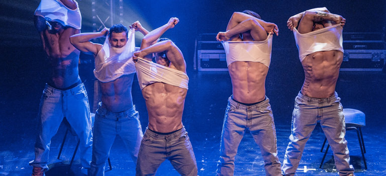 Some strippers taking their tops off on stage