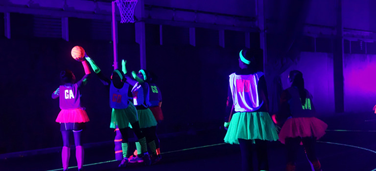 A group of women playing netball in the dark