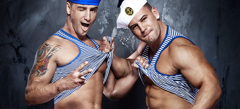two men dressed as sailors lifting up their tops showing six packs