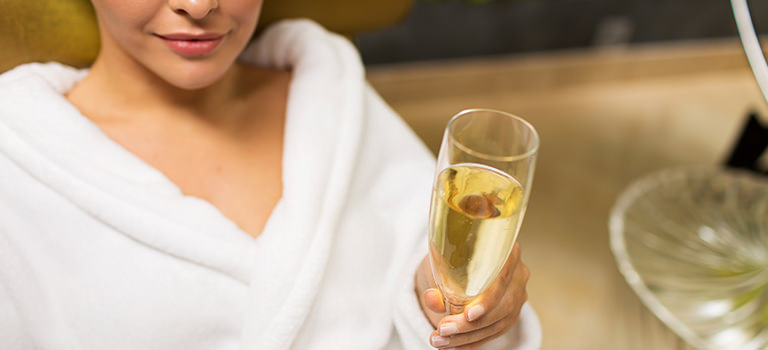 Woman drinking champagne in a robe at a spa on a hen do in Harrogate