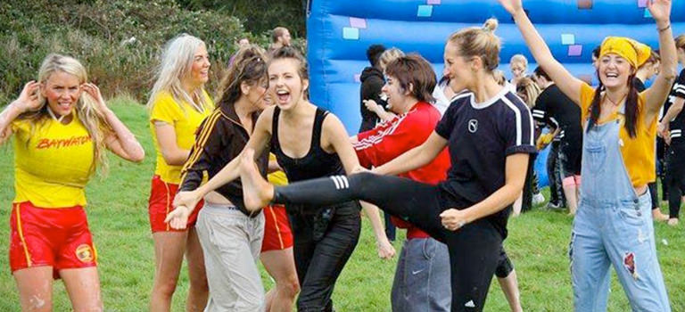 Women on hen party weekend taking part in a old school sports day activity in Newquay