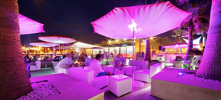 An outdoor bar area illuminated in purple