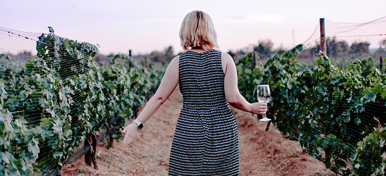 A girl with wine, walkin g through a field