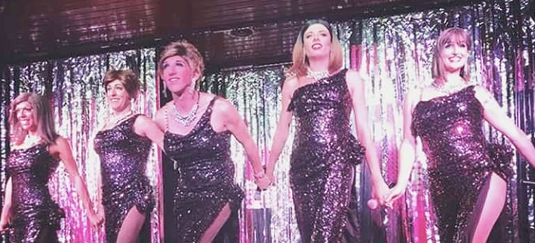 A group of women on stage in sparkly dresses
