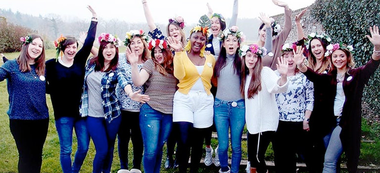 Group of women wearing flower crowns and posing for the picture