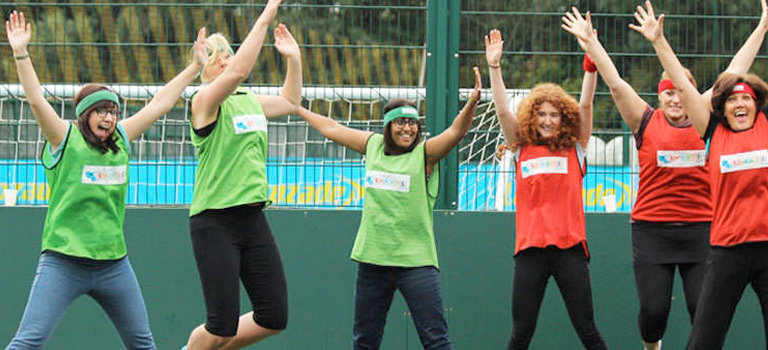 Group of women jumping with hands in the air wearing florescent sports bids
