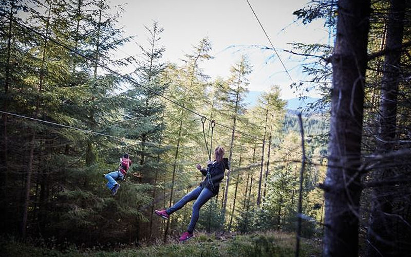 Two girls zipwiring through the forest