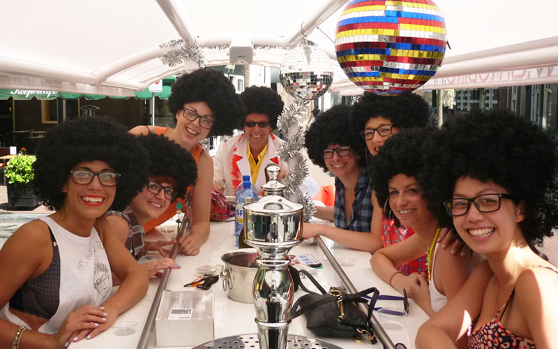 Some women wearing afro wigs under a disco ball in Amsterdam