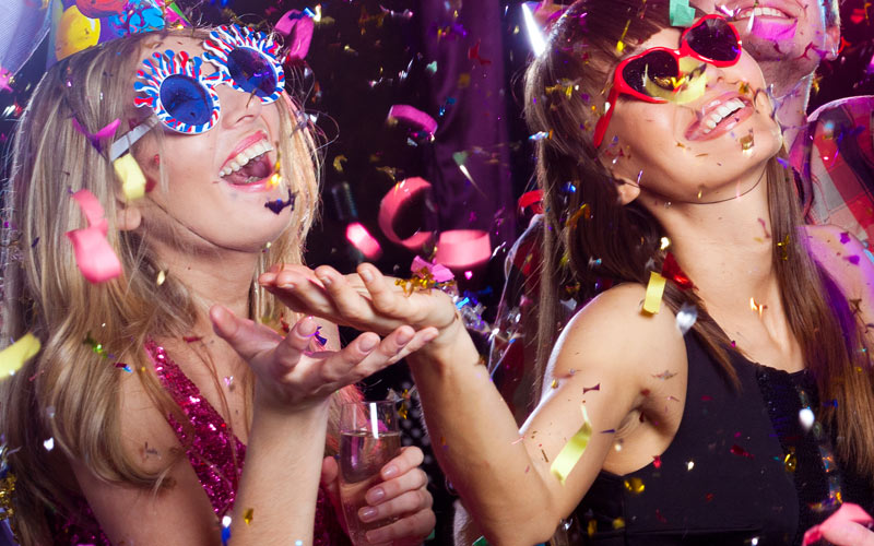 Some girls wearing sunglasses in a club, with confetti pouring down from the ceiling