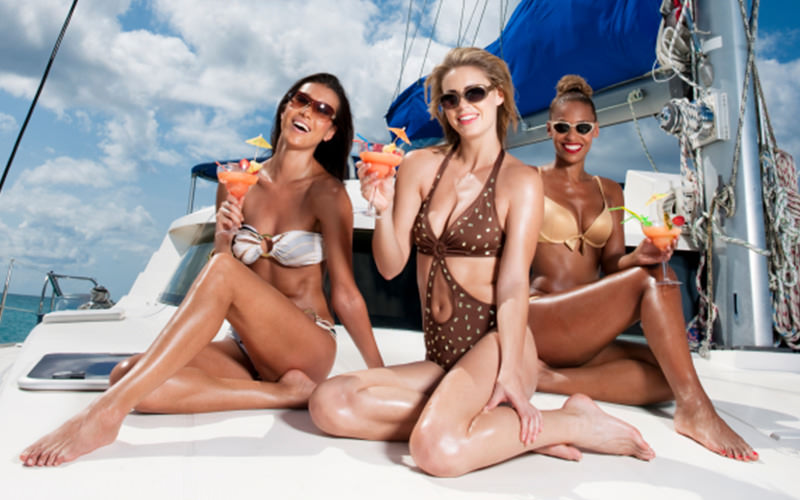 Three girls sipping cocktails on a yacht