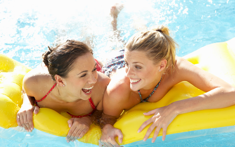 Two girls in theiur bikinis, laughing on a yellow lilo in the pool