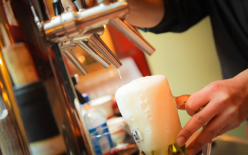 A frothy pint being poured