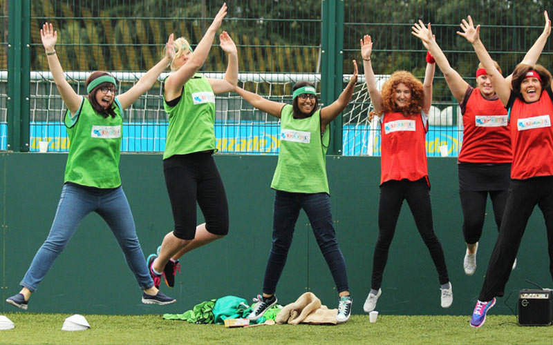 Women wearing red and green bibs, jumping in the air