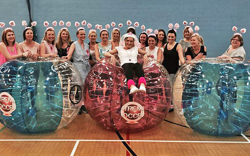 Some women posing with zorbs in bubble mayhen