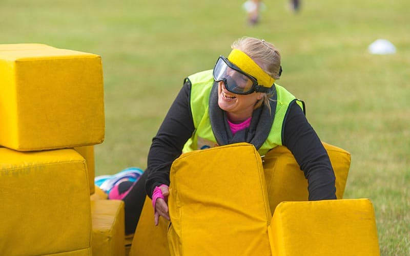 A woman playing on the obstacle course outside