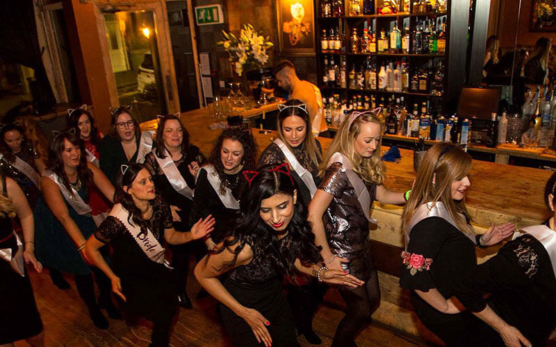A hen party dancing by a bar, all wearing cat ears