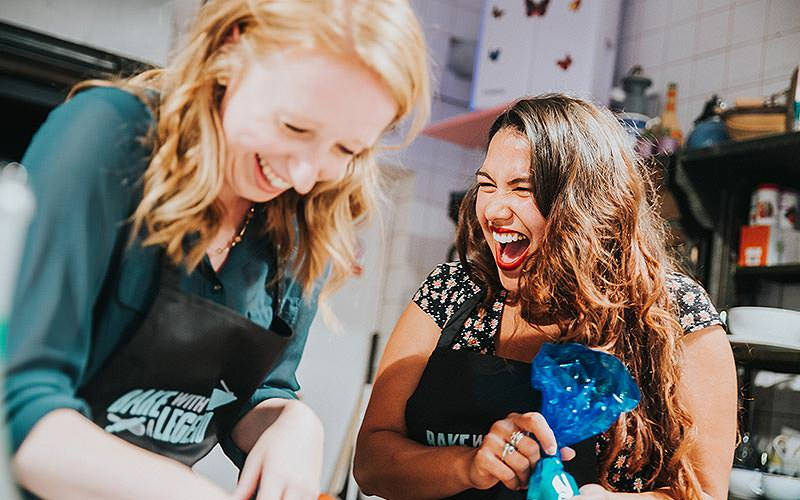 Two girls laughing with taking part in the Bake with a Legend activity